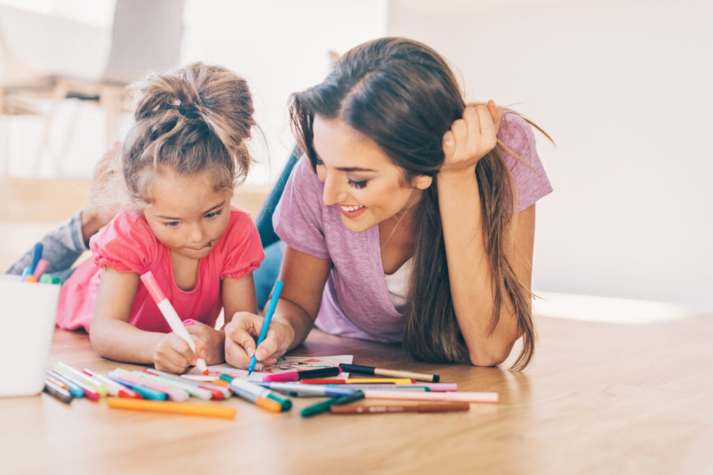 Mother and daughter coloring on the floor